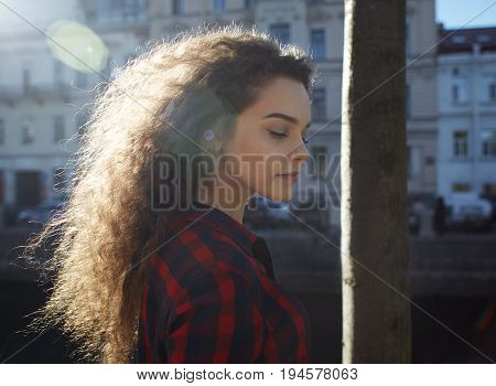 Profile portrait of attractive amazing young European woman model wearing stylish checkered shirt posing at tree and looking down while walking in park sun shining through her long loose hair