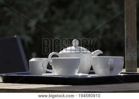 Summer garden afternoon tea party. White crockery tea set with china teapot cups and saucers on garden table.