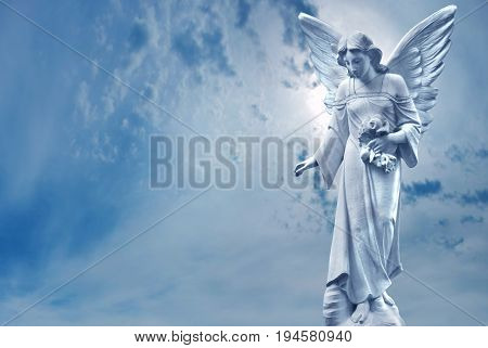 Angel sculpture on blue sky background concept of Religion