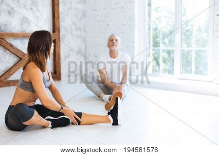 Do it slowly. Confident female sitting in semi position and touching her knee while doing stretching exercises