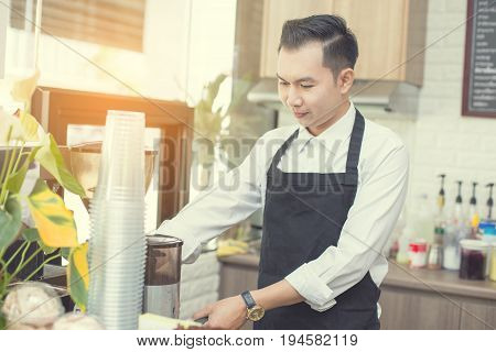 Asian barista man standing for making coffee cup with attractive smiling at coffee shop. Man with owner business concept. 30-40 years old. vintage tone.