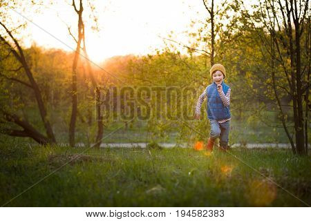 Portrait of smiling kid boy running in the park on sunset. Happy child walking outdoors on a sunny day. Lifestyle.