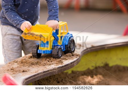 Closeup of toddler boy's hands playing with colorful toy tractor and sand in the park. Child playing with a car at a nursery or preschool. Child walking outdoors. Lifestyle.