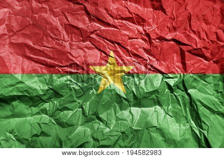 Burkina Faso flag painted on crumpled paper background