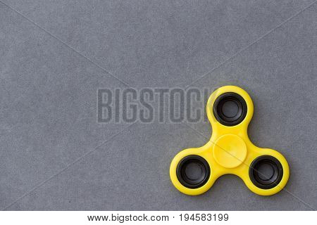 Yellow fidget spinner device on grey background. Top view. Playing with a yellow hand spinner fidget toy