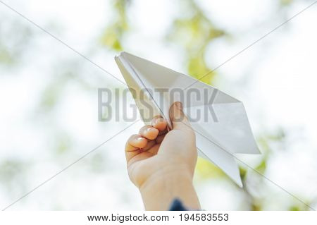 the plane of the paper in the hands of the child and the blue sky