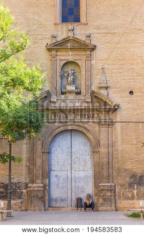 VALENCIA, SPAIN - JUNE 12, 2017: Homeless man sits on the doorstep of the Santa Ursula Church in Valencia, Spain
