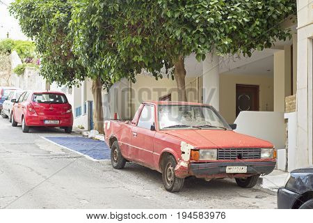Agis Nikolaos, Crete, Greece - June 13, 2017: Old rusty red car parked in the street