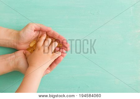 Top view on child's hand taking capsules Omega 3 from mother's hands on turquoise background. fish fat oil capsules. Health concept
