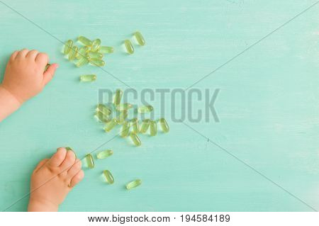 Top view on child's hands taking capsules Omega 3 on turquoise background.