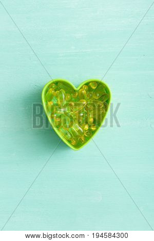 Top view on green plastic heart shape with pile of capsules Omega 3 on turquoise background. fish fat oil capsules. Health concept