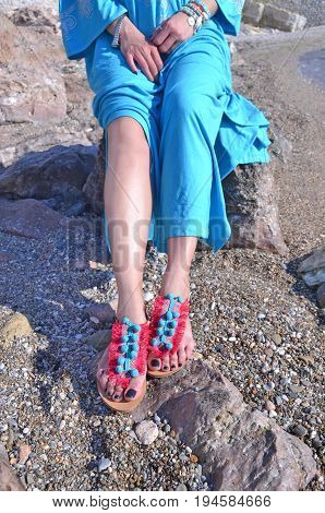 model advertises bohemian sandals clothes and accessories at a greek beach
