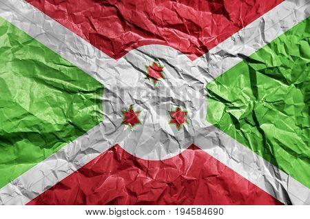 Burundi flag painted on crumpled paper background