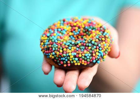 Calorie bomb symbol, with a multicolored appetizing donut in woman hand