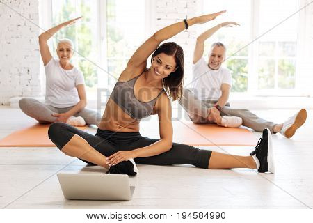 Sport with pleasure. Happy elderly people sitting on mats behind their instructor and lifting arms while keeping smile on faces