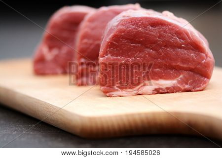 Appetizing raw beef or veal meat on wooden cutting board