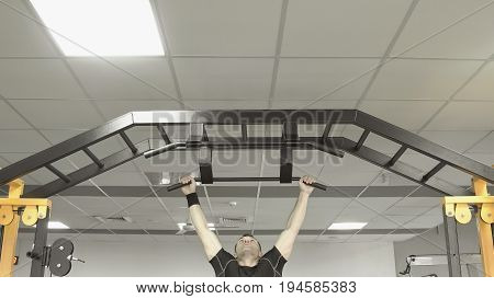 Athlete Muscular Fitness Male Pulling Up On Horizontal Bar In A Gym