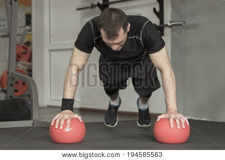 Fitness Man Doing Push-ups Exercise On The Ball In Gym
