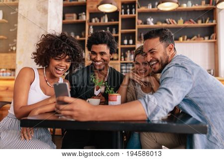 Group Of Friends Meeting At Cafe Using Cell Phone