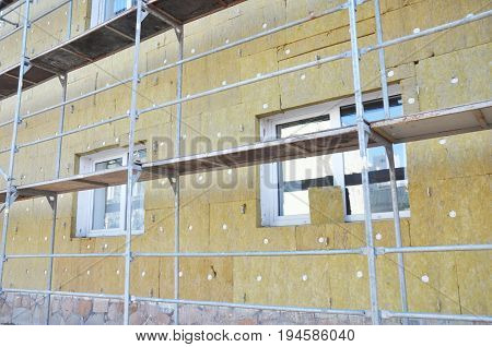 Install Rock Mineral Wool Insulation. Energy efficiency house wall renovation for energy saving. Exterior house wall heat insulation with mineral wool building under construction.