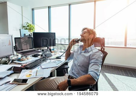 Business Investor In A Happy Mood Talking Over Phone In Office.