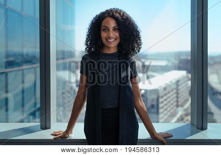 Smiling businesswoman standing in her office in a highrise building overlooking the cityscape. Woman with curly hair standing near window in office.