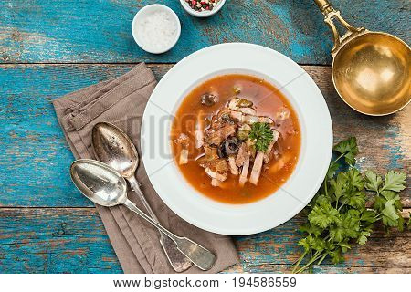 Soup with meat, olives, herbs, lemon in white bowl, black bread and spices on rustic wooden background, top view homemade food. Traditional Russian soup - solyanka