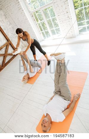 Train with pleasure. Attractive sportswoman standing near her visitor and bowing her head while supporting