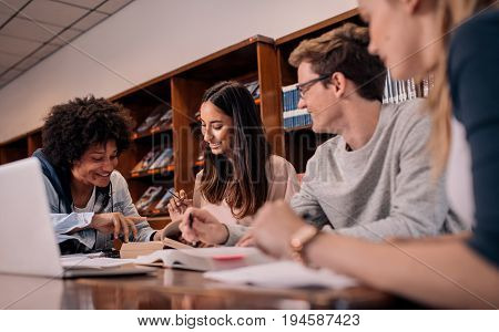 Young people sitting at table reading reference books for study notes. Group of young students doing assignment in library.