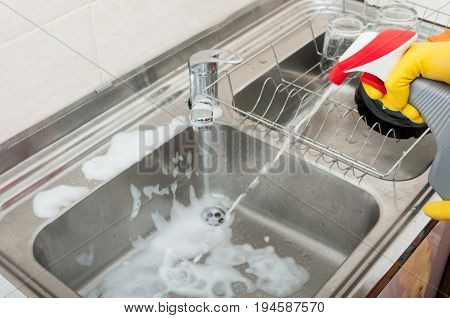 Housekeeping Person Washing The Sink With Cleaning Spray