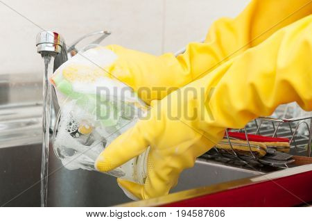 Hands Of Woman Washing Dishes In The Kitchen
