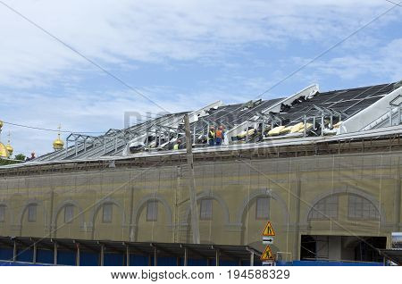 Builders assemble the roof of the building in the summer under blue sky