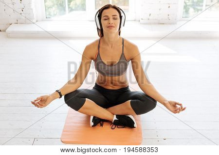 Meditate with music. Positive delighted yoga instructor sitting on the mat and keeping eyes closed while expressing calmness