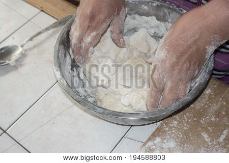 Close up view of baker kneading dough. Hands preparing dough in metal cup. Woman hands kneading fresh dough.