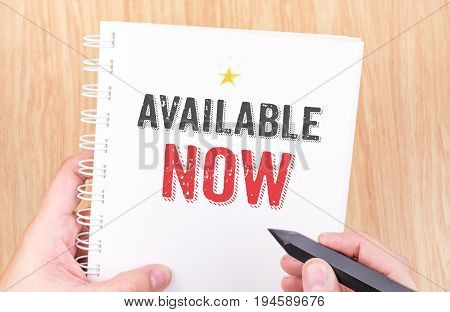 Available Now Word On White Ring Binder Notebook With Hand Holding Pencil On Wood Table,business Con