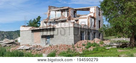 The old destroyed brick multi-storey building. Destroyed Ruined Building. Asubulak, Kazakhstan