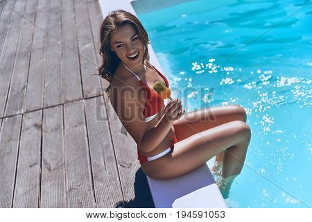 Enjoying warm day. Beautiful young woman in swimwear holding an ice-cream and smiling while sitting by the pool outdoors