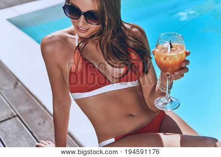 Cooling off with a cocktail. Attractive young woman in swimwear holding a glass while sitting by the pool outdoors