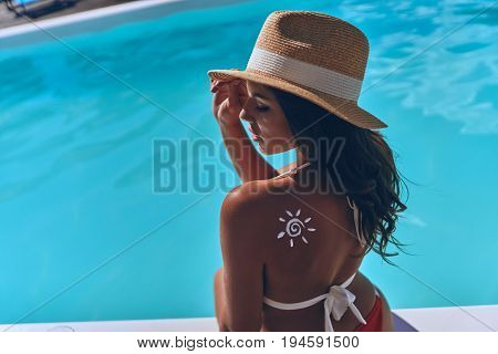 Protection from sun. Rear view of young woman with a drawn sun on her shoulder sunbathing while sitting by the pool outdoors
