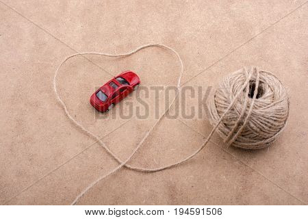 Red Toy Car And A Spool Of Thread Form A Heart Shape