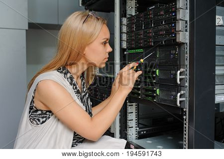 Young Woman Engineer It With A Screwdriver Between The Server Racks In The Data Center