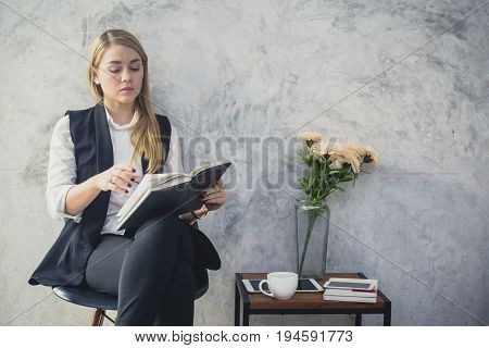 Portrait of a beautiful young woman reading book 20-30 year old.