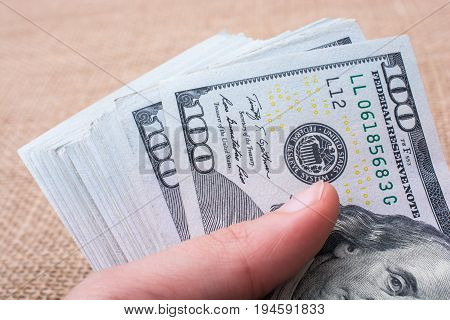 Hand holding banknote bundle of US dollar on a linen canvas background