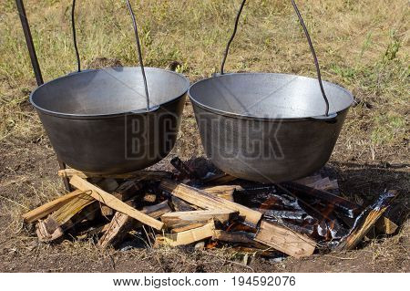 Cooking plov in the cauldron. Only the meat in the cauldron. Field kitchen. Eastern cuisine.