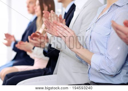 Close up of business people hands clapping at conference.