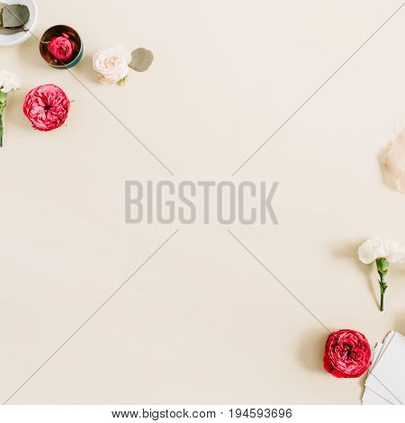 Flowers border frame made of beige and red roses and white carnation on pale pastel beige background. Flat lay top view. Floral texture background.