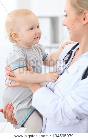Pediatrician is taking care of patient in hospital. Female doctor holds toddler girl at hands. Health care, insurance and help concept.