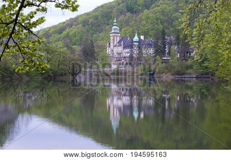 Lillafured palace (Miskolc Hungary) and lake. Mountains are covered with lush spring foliage.