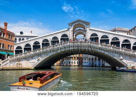 Venice, Italy - May 18, 2017: Water taxis are sailing along the Grand Canal to the Rialto Bridge. Rialto Bridge is one of the main tourist attractions in Venice.