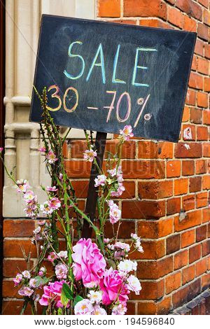 Percentage of discounts on a black graphite board near a bush of roses in front of the store entrance. Riga